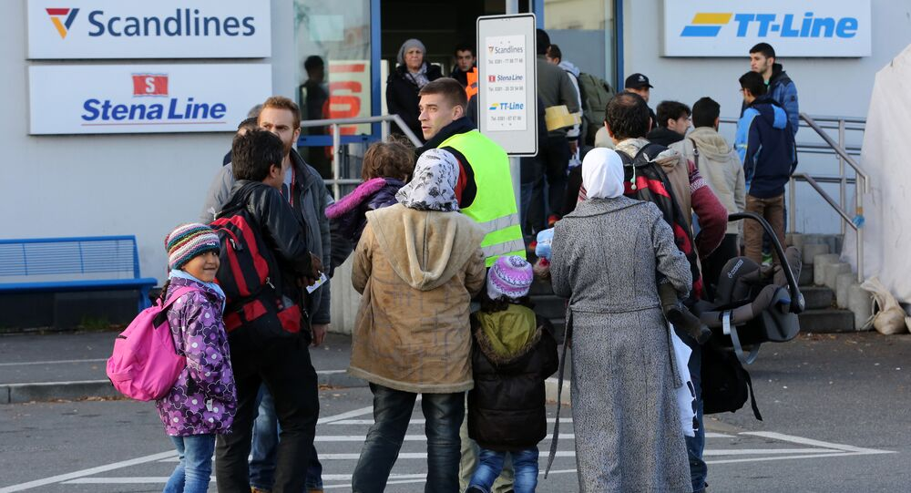 Migrants go to the ferry terminal to buy tickets at the port of Rostock, northeastern Germany