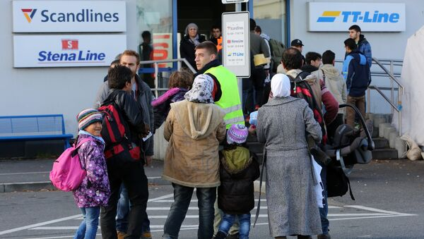 Migrants go to the ferry terminal to buy tickets at the port of Rostock, northeastern Germany - Sputnik International