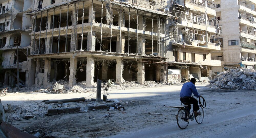 A man rides a bicycle near damaged buildings in the rebel held besieged al-Sukkari neighbourhood of Aleppo, Syria October 19, 2016.