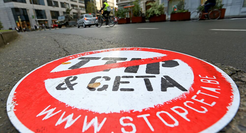 A cyclist rides past a placard reading  STOP TTIP CETA outside the EU Council headquarters ahead of a European Union leaders summit in Brussels, Belgium October 20, 2016.