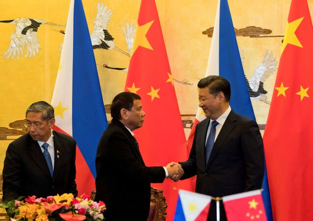 Philippine President Rodrigo Duterte and Chinese President Xi Jinping (R) shake hands after a signing ceremony held in Beijing, China, October 20, 2016