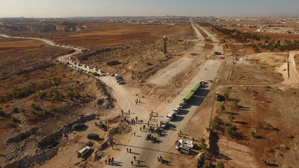 Law enforcement officers near cars and ambulances in a humanitarian corridor along the Castello Road in northern Aleppo, Syria