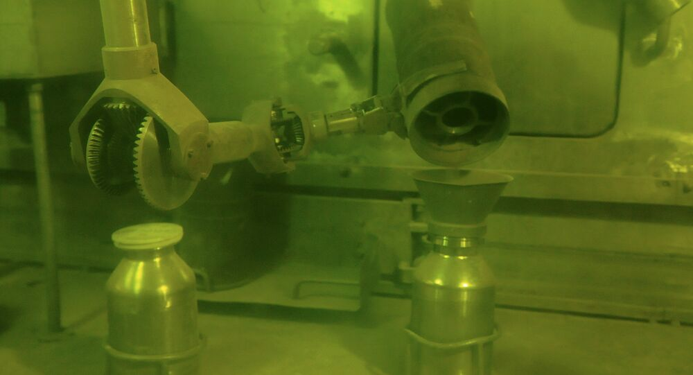 Operator putting plutonium dioxide powder in a container for storage and processing using handler.