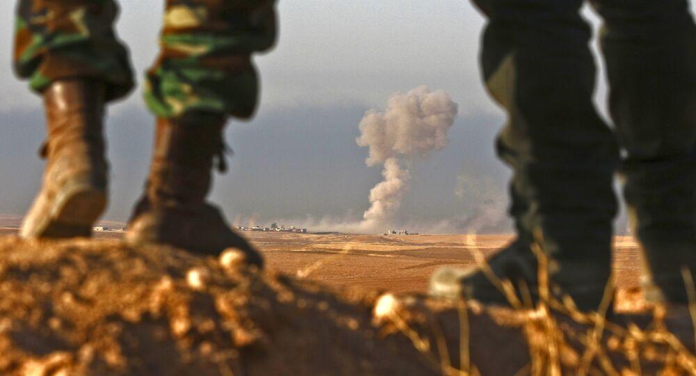 Iraqi Kurdish Peshmerga fighters stand in an area near the town of Bashiqa, some 25 kilometres north east of Mosul