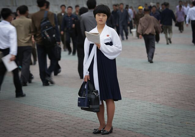 A North Korean student pauses to study as other people make their way to work during morning rush hour