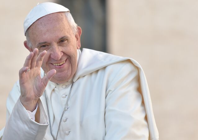 Pope Francis waves to the crowd as he arrives for his weekly general audience at St Peter's square in Vatican