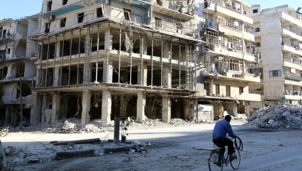 A man rides a bicycle near damaged buildings in the rebel held besieged al-Sukkari neighbourhood of Aleppo, Syria. (File) - Sputnik International