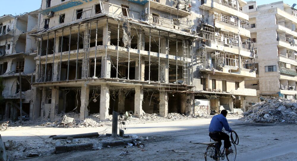 A man rides a bicycle near damaged buildings in the rebel held besieged al-Sukkari neighbourhood of Aleppo, Syria. (File)