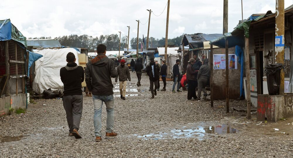 Migrants walks through the Jungle migrant camp in Calais, northern France, on October 22, 2016