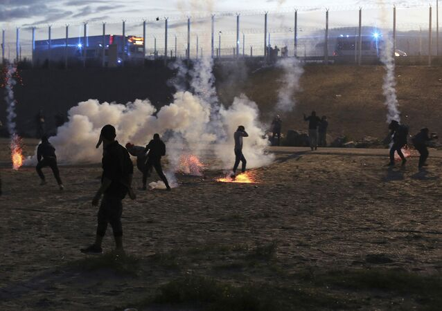 French riot police officers fire tear gas canisters during clashes with migrants in a makeshift migrant camp near Calais, France, Saturday, Oct. 22, 2016