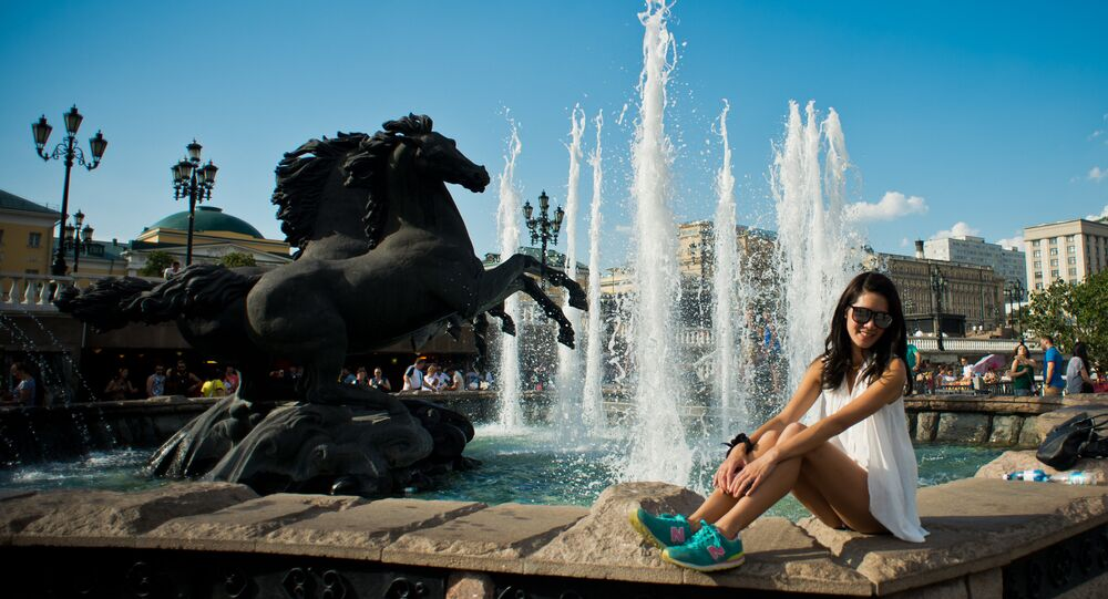 Tourists pose for photos at the Four Seasons fountain on Manezh Square
