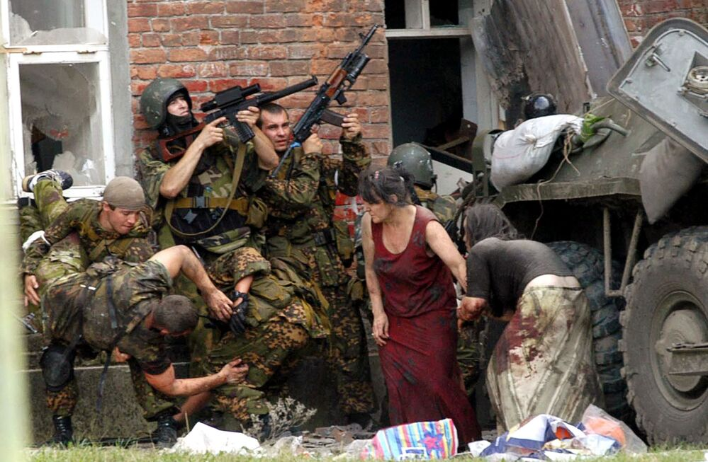 A Russian special police soldier (L) carries an injured colleague as two soldiers and two women take cover behind the APC during the Beslan School rescue operation, northern Ossetia, September 3, 2004.