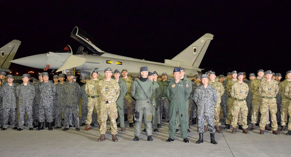 British Royal Air Force's soldiers pose with Japan Air Self-Defense Force soldiers for a photograph in front of a Typhoon Eurofighter jet upon their arrival to participate in a joint military drill with Japan's air force, at Misawa air base in Misawa, Aomori prefecture, Japan, in this photo taken by Kyodo October 22, 2016