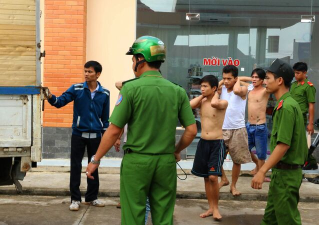 Authorities escort drug addicts (back R) as they prepare to board a truck after being rearrested after escaping from a compulsory rehabilitation centre in the southern Vietnamese province of Dong Nai on October 24, 2016