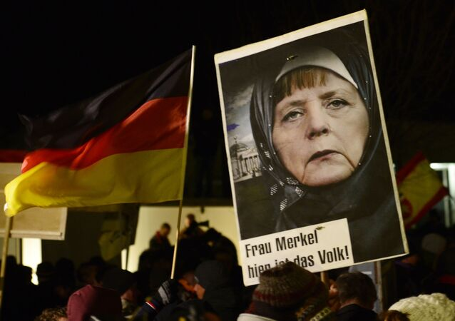 A protestor holds a poster with an image of German Chancellor Angela Merkel wearing a headscarf in front of the Reichstag building with a crescent on top during a rally of the group Patriotic Europeans against the Islamization of the West, or PEGIDA, in Dresden, Germany, Monday, Jan. 12, 2015