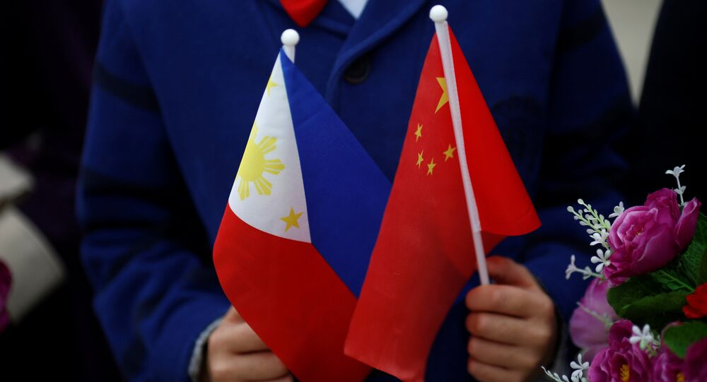 Children hold plastic flowers, national flags of China and the Philippines before President of the Philippines Rodrigo Duterte and China's President Xi Jinping attend a welcoming ceremony at the Great Hall of the People in Beijing, China, October 20, 2016