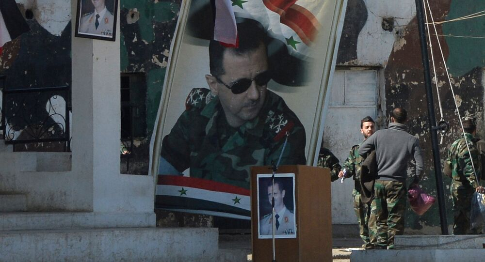 Banners with the portrait of Syrian President Bashar al-Assad at a self-defense fighters' training center near Damascus