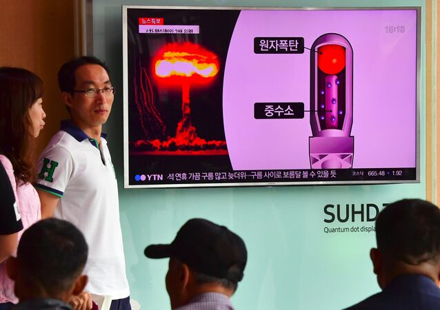 People watch a television news report on North Korea's latest nuclear test at a railway station in Seoul on September 9, 2016