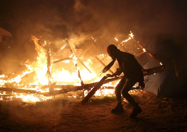 A migrant is seen in silhouette near flames from a burning makeshift shelter on the second day of the evacuation of migrants and their transfer to reception centers in France, as part of the dismantlement of the camp called the Jungle in Calais, France, October 25, 2016