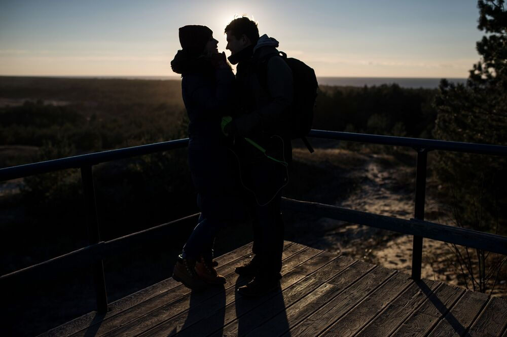 Young people at a viewing point in Curonian Spit National Park. The observation deck is situated at the highest point of the Bolotnaya dune, or Bruhberg dune, offering a beautiful view of the forest, the sea and the bay.