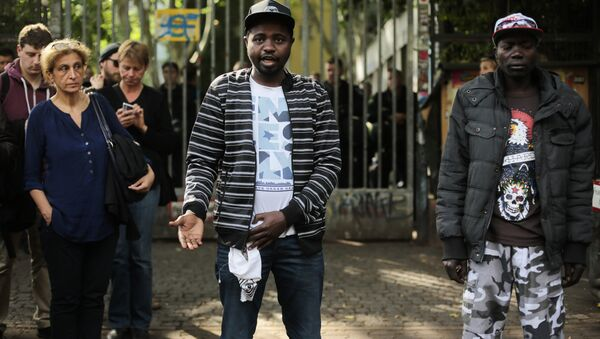 Sudanese refugees, who said their names are Adam, center, and Anour, right, speak to media in front of the entrance of the occupied Gerhart Hauptmann School in Berlin, Germany, Friday, June 27, 2014 - Sputnik International