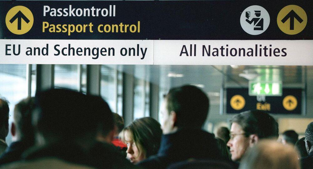 Travellers queue for passport control at Stockholm airport Arlanda