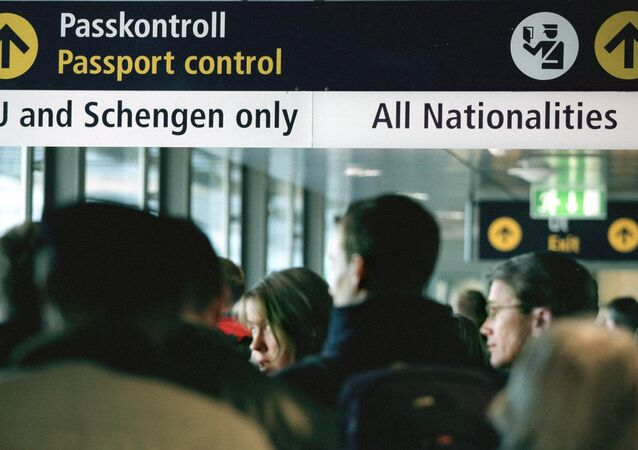 Travellers queue for passport control at Stockholm airport Arlanda