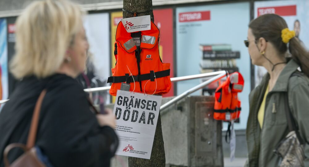 Women pass by a life vest and a placard reading Borders kill hanging on a tree in Stockholm as part of an action by Swedish branch of humanitarian NGO Doctors without borders, in solidarity with migrants seeking asylum in Europe after fleeing their home countries on September 14, 2015