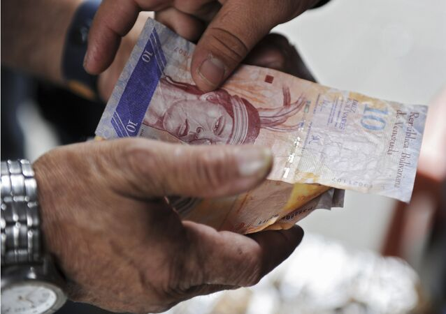 A man receives Venezuelan currency bills in Caracas on November 30, 2011.