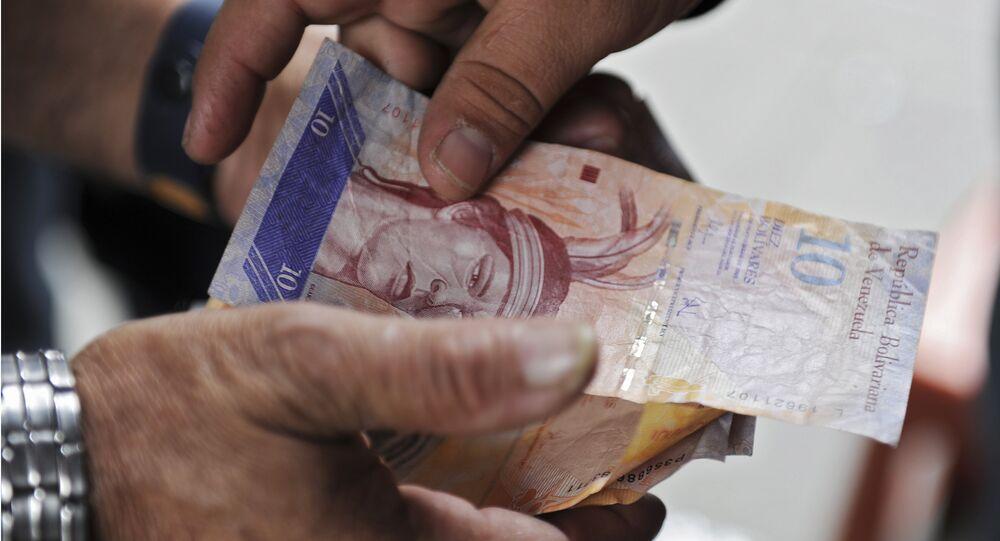 A man receives Venezuelan currency bills in Caracas on November 30, 2011.