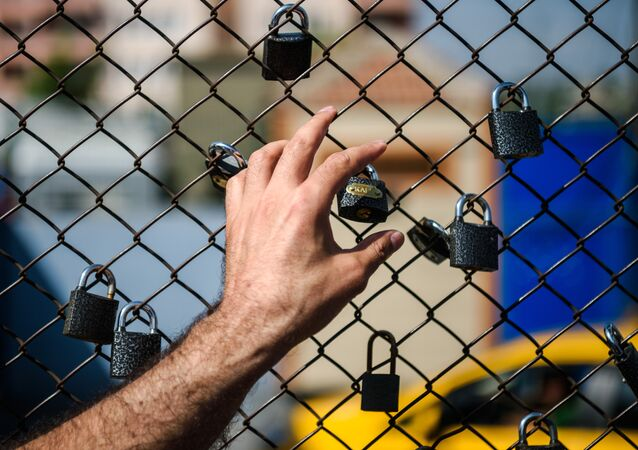 A demonstrator puts his hand on a fence with padlocks left by prisoners during a demonstration in front of the Metris prison on June 24, 2016 in Istanbul.