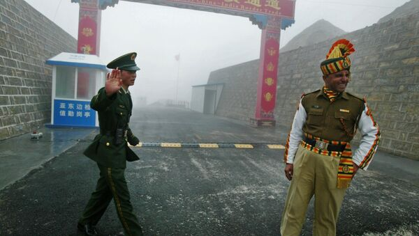 Chinese soldier (L) and an Indian soldier stand guard at the Chinese side of the ancient Nathu La border crossing between India and China. - Sputnik International