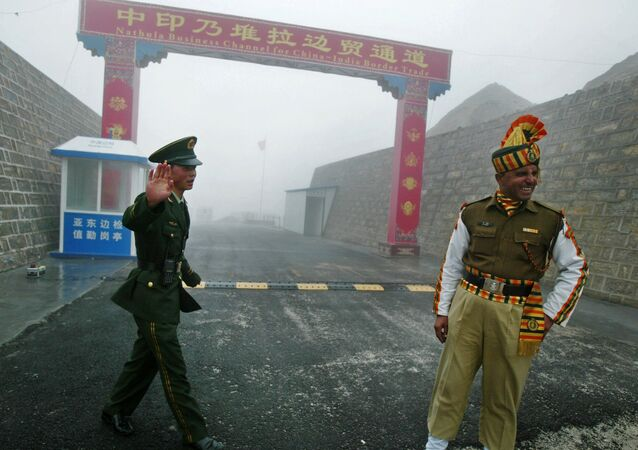 Chinese soldier (L) and an Indian soldier stand guard at the Chinese side of the ancient Nathu La border crossing between India and China.