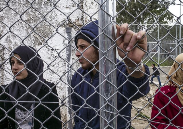 Syrian refugees stand inside the Moria camp during the demostration against the deal between EU and Turkey, on March 24, 2016 in Lesbos.