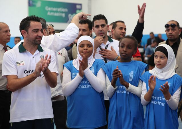 Former Barcelona football player Xavi Hernandez (L), who currently plays for Al-Sadd in the Qatar Stars League, claps during a football training as he visits the al-Baqaa Palestinian refugee camp near Amman on September 29, 2016.