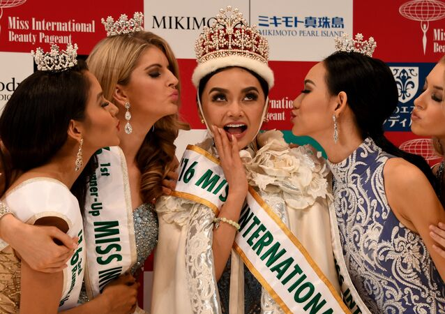Newly elected 2016 Miss International Kylie Verzosa from Philippines (C) receives a kiss from 3rd runner-up Miss Nicaragua Brianny Chamorro (L), 1st runner-up Miss Australia Alexandra Britton (2nd L), 2nd runner-up Miss Indonesia Felicia Hwang (2nd R) and 4th runner-up Miss USA Kaitryana Leinbach (R) during the Miss International beauty pageant final in Tokyo on October 27, 2016