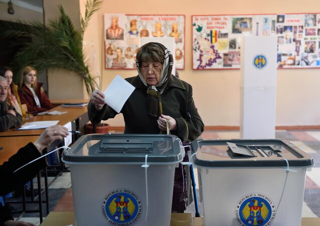 A woman casts her ballot for the presidential election at a polling station in Chisinau city