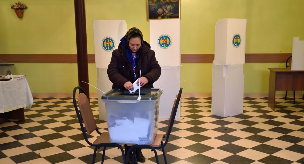 A voter casts her ballot at a polling station in Scoreni village, Moldova, on October 30, 2016.