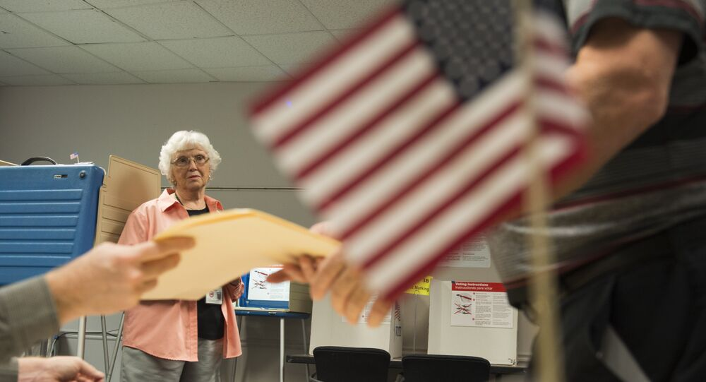 An election official watches as a man takes a ballot at an in-person absentee voting station in Fairfax, Virginia on October 12, 2016