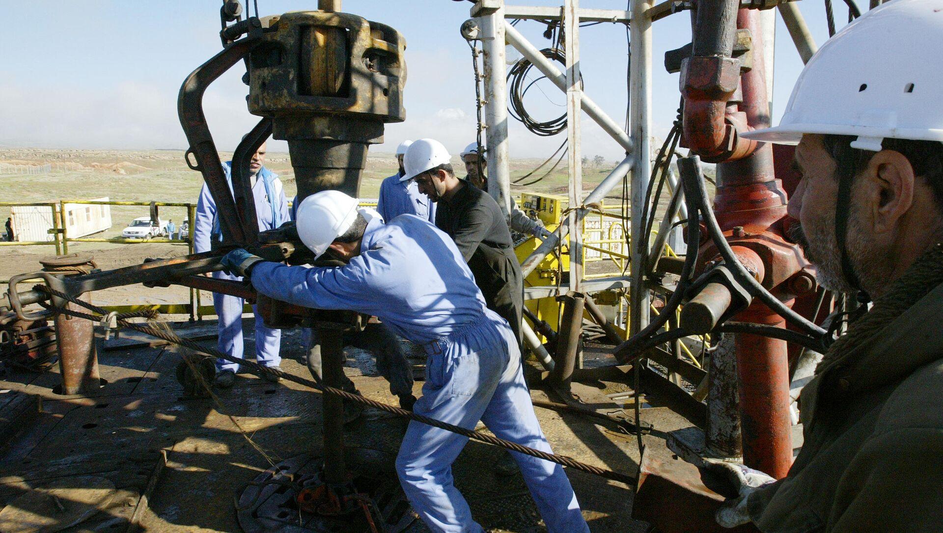 Iraqi workers pump oil at the Shirawa oilfield, where oil was first pumped in Iraq in 1927  - Sputnik International, 1920, 05.09.2021