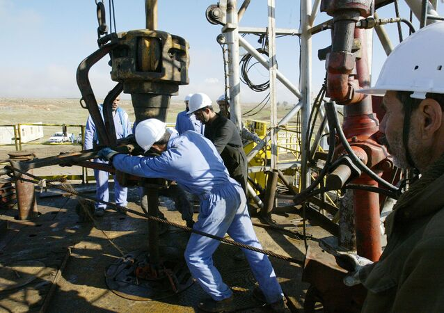 Iraqi workers pump oil at the Shirawa oilfield, where oil was first pumped in Iraq in 1927