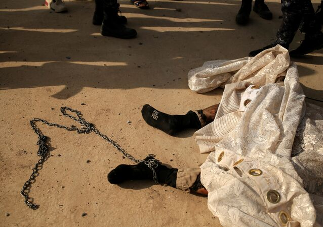 A chain is attached to the foot of a dead Islamic State fighter's body along a street of the town of al-Shura, south of Mosul, Iraq October 30, 2016