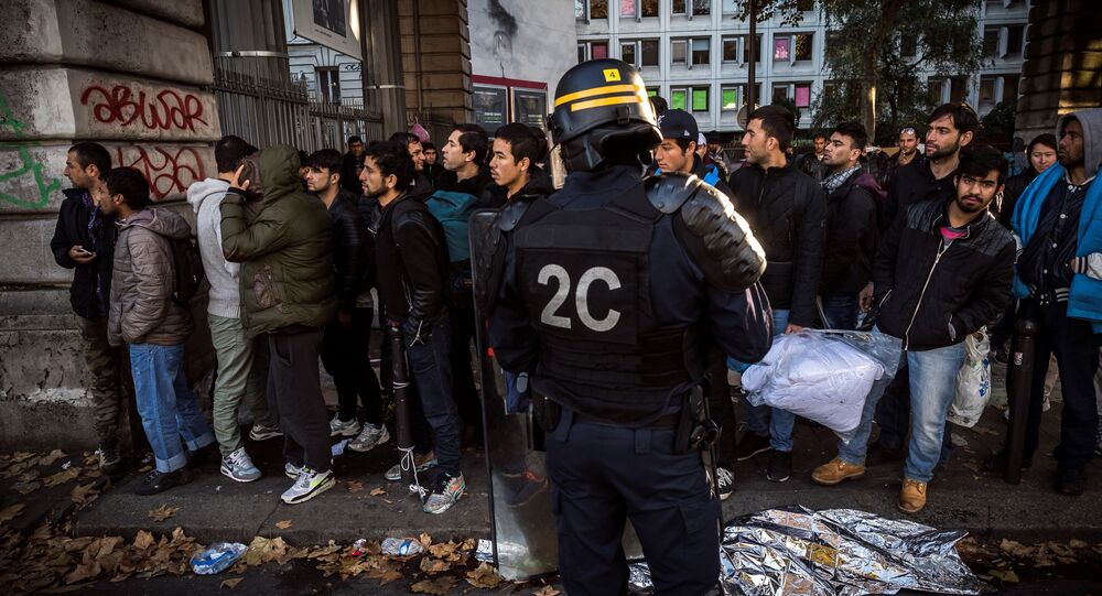 A French anti-riot policeman stands in front of migrants near the Jaures and Stalingrad metro stations, in northern Paris on October 31, 2016, during a police operation aiming at a future evacuation of a migrant camp