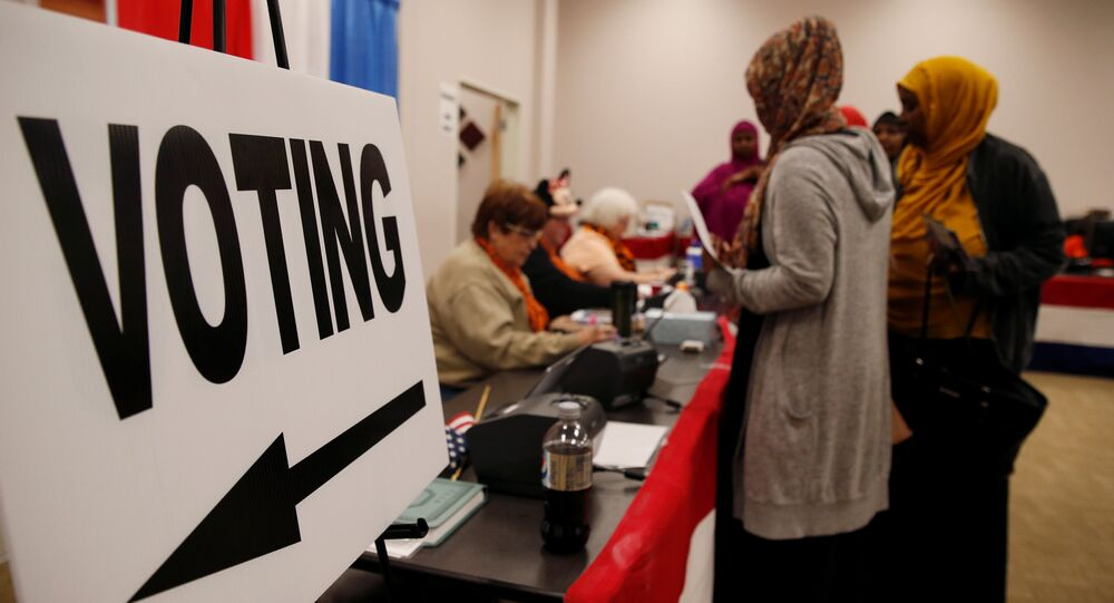 Voters stand near a voting sign before casting ballots during early voting at the Franklin County Board of Elections in Columbus, Ohio U.S., October 28, 2016