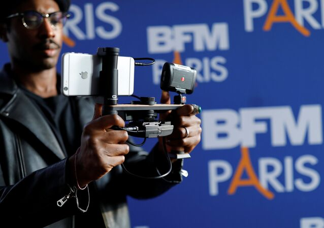 A video journalist uses an Apple iPhone 7 Plus smart phone to film during a press conference for the launching of the news channel, BFM Paris, in Paris, France, October 13, 2016