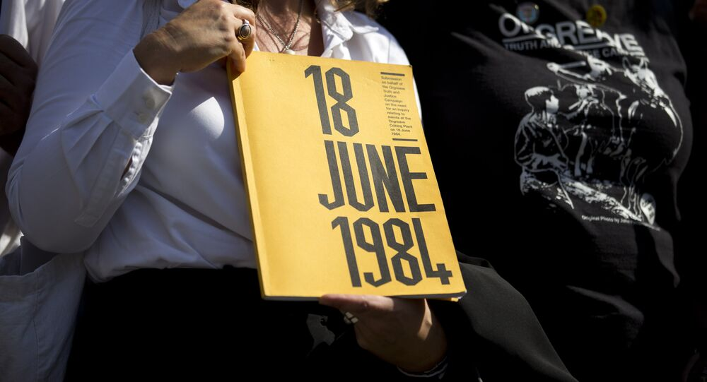 A campaigner holds a book on which the cover reads 18 June 1984 as she stands outside the Houses of Parliament in central London on September 13, 2016, during a protest calling for an inquiry into the 'Battle of Orgreave' and the policing of the miners' strikes