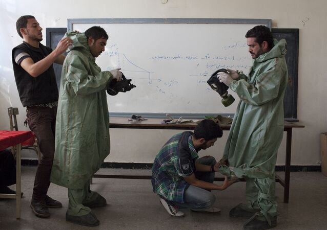 An Aleppo University student, shows Syrian citizens hows to put protective gear as he instructs them with rudimentary means of how to respond to a chemical attack, in the northern Syrian city of Aleppo (File)