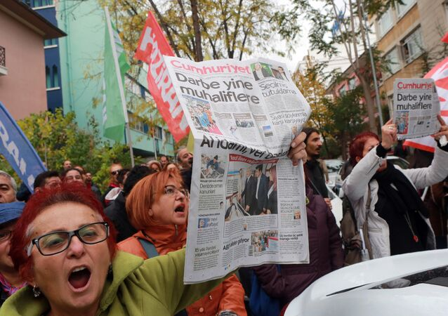 Participants hold the latest copy of Turkish newspaper Cumhuriyet outside the headquarters in Ankara on October 31, 2016, during a protest against the detention of the newspaper's editor-in-chief and a dozen journalists and executives