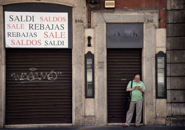 A man stands outside a closed shop indicating sales, in the shopping street of Via del Corso, in central Rome on July 3, 2016