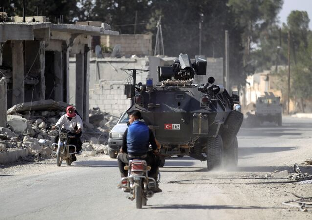 Men ride motorbikes past a Turkish armored carrier in the northern Syrian rebel-held town of al-Rai, in Aleppo Governorate, Syria, October 5, 2016